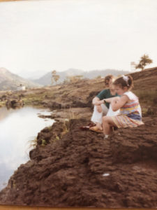 A woman and a girl sit by the side of a river
